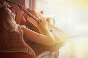 Eine junge Frau sitzt bequem auf einem Stuhl und verbringt die Zeit mit Gitarre üben oder spielen