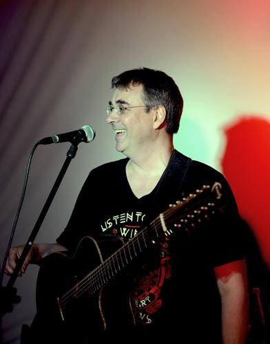 Singer-Songwriter Peter Bachmann mit Gitarre, vor Mikrofonständer.