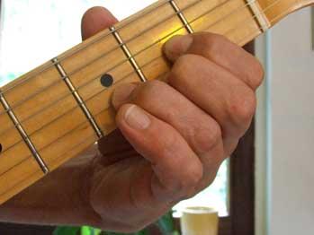 Foto von linker Hand auf Gitarrenhals, im Hintergrund der Daumen