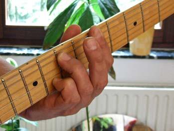 Ein Gitarrenhals mit Greifhand, der Daumen liegt gegenüber vom Mittelfinger auf der Halsrückseite
