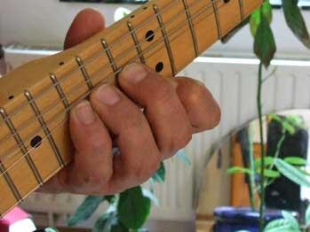 Gitarrenhals mit linker Greifhand, die die Saiten zieht, der Daumen ist schräg nach oben aufgerichtet