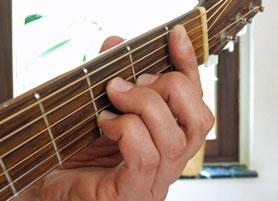 Hals einer akustischen Gitarre von vorne, der Daumen im Hintergrund.