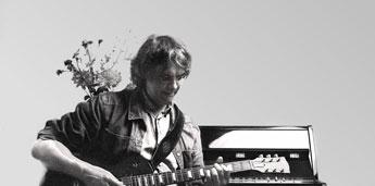 Schwarzweißfoto von Gitarrenlehrer Peter Bachmann mit E-Gitarre vor Klavier sitzend